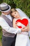 拥抱新娘的帽子的新郎 免版税库存照片