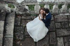 拥抱新婚佳偶新娘从后面的英俊的肉欲的新郎在老 免版税库存图片