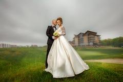 拥抱有吸引力的年轻典雅的merried的夫妇户外 免版税库存图片