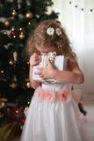拥抱有礼物的白色礼服的愉快的小女孩一个箱子 免版税库存照片