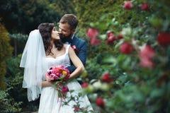 拥抱有花束的愉快的新郎美丽的新娘从后面nea 免版税库存图片