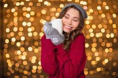 拥抱杯子温暖的茶和微笑的迷人的逗人喜爱的夫人 免版税库存照片