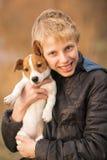 拥抱杰克罗素小狗的男孩 图库摄影