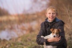 拥抱杰克罗素小狗的男孩 库存照片