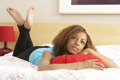 拥抱枕头的卧室女孩少年 免版税库存图片