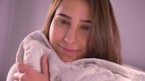 拥抱枕头的年轻可爱的白种人女性特写镜头画象看微笑和修理她的头发的照相机 股票视频