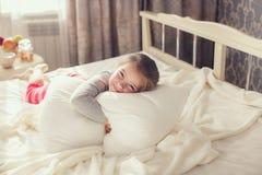 拥抱枕头的一个小女孩的画象 库存图片