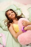拥抱枕头的女孩 免版税库存图片
