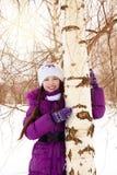 拥抱树的愉快的女孩 图库摄影