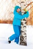 拥抱树的愉快的女孩 免版税库存图片