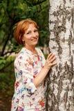 拥抱桦树的一名中年可爱的平静的妇女的画象 免版税图库摄影