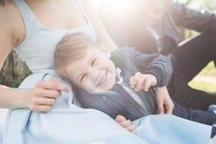 拥抱步行的妈妈一个孩子在公园 库存图片