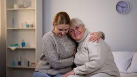 拥抱残疾祖母,在家庭的支援关系的关心的女孩 免版税库存图片