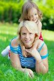 拥抱母亲公园的女儿 免版税库存图片