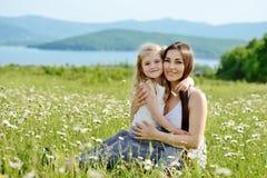 拥抱母亲的女儿 库存照片