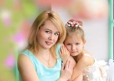 拥抱母亲的小女儿 免版税库存照片