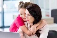 拥抱母亲的小女孩与膝上型计算机一起使用 免版税库存照片