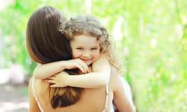 拥抱母亲的愉快的女儿在自然的温暖的晴朗的夏日 免版税库存图片