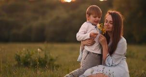 拥抱母亲的男孩在日落在夏天,一个爱恋的儿子和幸福家庭接触 影视素材
