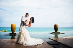 拥抱海洋背景的新郎新娘  浪漫婚礼照片 免版税图库摄影
