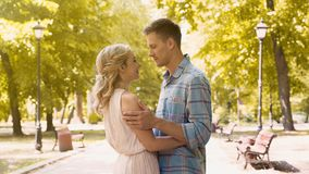 拥抱爱恋的夫妇轻轻地,享受期待已久的日期在公园,第一爱人 免版税库存照片