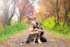 拥抱爱犬的平安的妇女,当在步行在森林时 库存图片