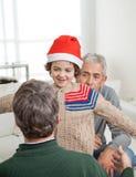 拥抱父亲的圣诞老人帽子的儿子 库存图片