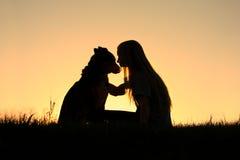 拥抱狗剪影的妇女 免版税库存图片