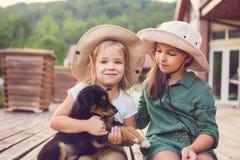 拥抱狗小狗的两个逗人喜爱的妹 库存照片