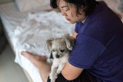 拥抱狗的亚裔妇女很逗人喜爱在床上在卧室 库存照片