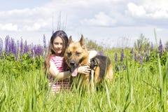 拥抱狗的女孩户外 免版税库存照片