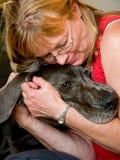拥抱狗的妇女 免版税库存图片