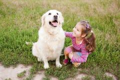 拥抱狗的愉快的小女孩 图库摄影