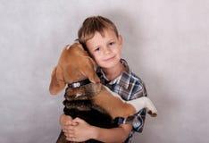 拥抱狗的欧洲男孩小猎犬 库存照片