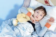 拥抱玩具熊的一个病的男孩的画象 免版税库存图片