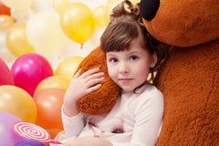 拥抱玩具熊的可爱的小女孩画象  库存图片