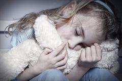 拥抱玩具熊的哀伤的女孩 免版税库存图片