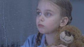 拥抱玩具熊的孤独的逗人喜爱的女孩在多雨窗口后的孤儿院,作梦 股票录像