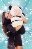 拥抱玩具熊的微笑的兴奋的女商人 图库摄影