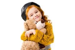 拥抱玩具熊的愉快的红色头发孩子 免版税库存照片