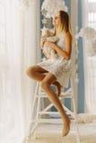 拥抱玩具熊的沉思少年的垂直的照片,当坐椅子和看通过窗口时 库存照片