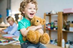拥抱玩具熊的逗人喜爱的小孩 免版税库存图片