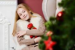 拥抱玩具的美丽的圣诞节女孩坐在一把白色椅子在壁炉和圣诞树附近 库存照片