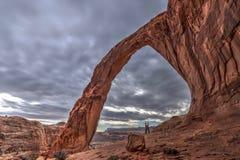 拥抱由自然曲拱的年轻夫妇在日落 免版税库存照片