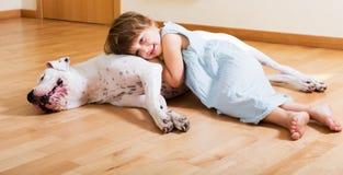 拥抱白色狗的小女孩 免版税库存照片