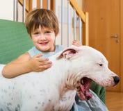 拥抱白色狗的小女孩 免版税库存图片