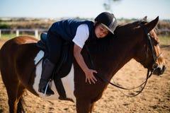 拥抱白马的微笑的男孩在大农场 库存图片