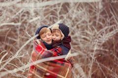 拥抱的两个微笑的兄弟用一条温暖的毯子盖了在一个冬日 免版税库存图片