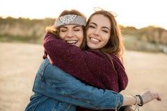 拥抱的两个微笑的女性朋友 免版税库存图片