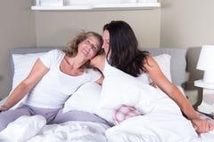 拥抱的两名可爱的妇女在床上 库存照片